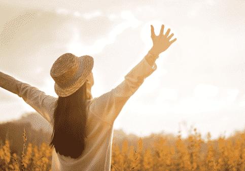 Frau sich sonnend mit Hut und ausgebreiteten Armen der Sonne entgegen gehend