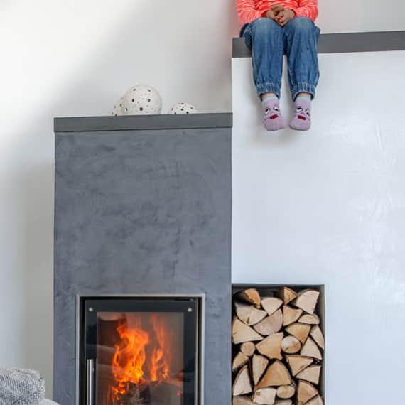 Kind sitzt auf einer Mauer neben dem Ofen.