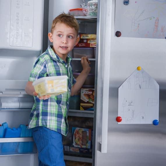 Ein Kind steht vor dem offenen Kühlschrank