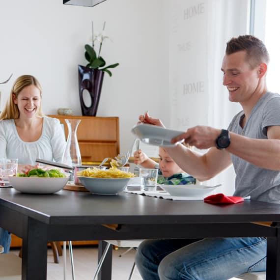 Glückliche, dreiköpfige Familie sitzt zum Essen bei Tisch