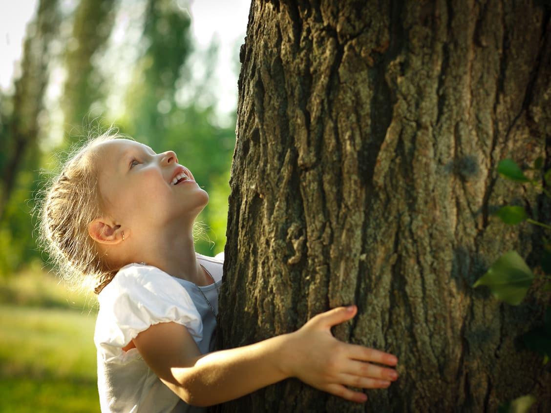 Kind das einen Baum umartm