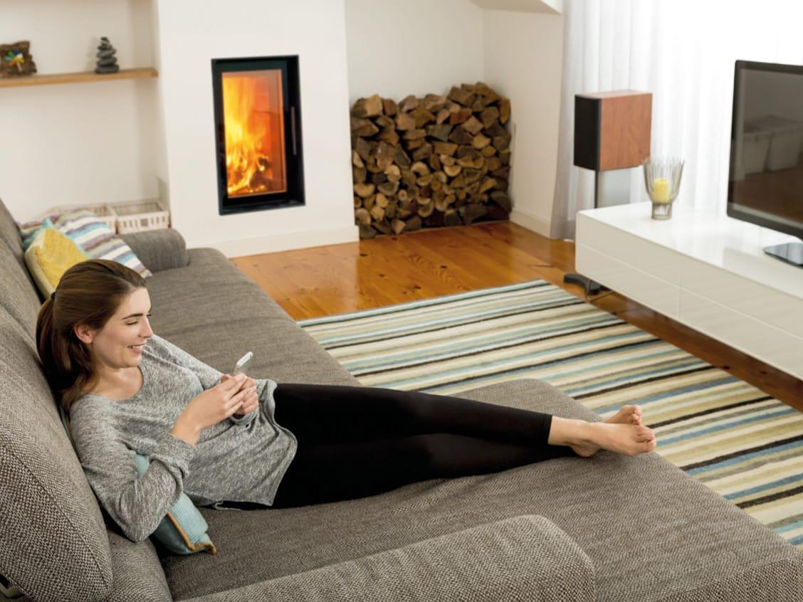 Dame liegt auf einer Wohnzimmerbank vor einem Ofen