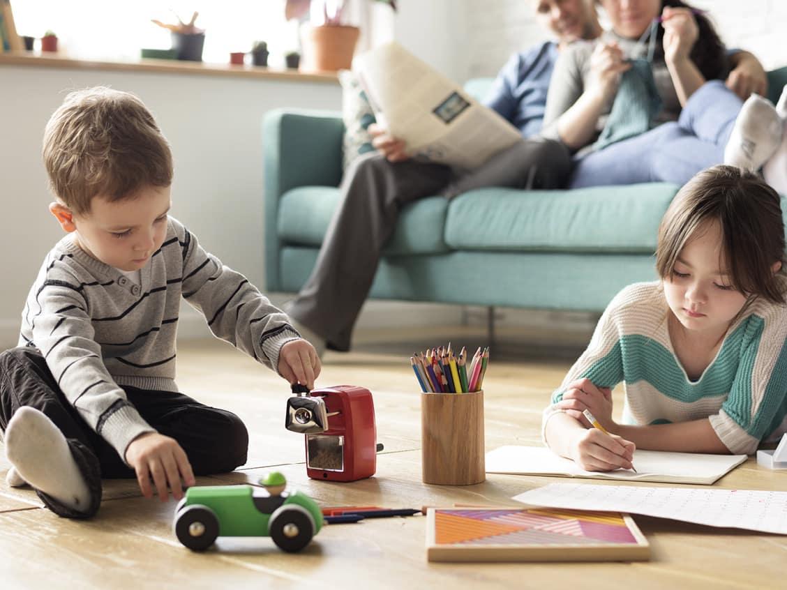Zwei Kinder zeichnen mit Farbstiften am Boden