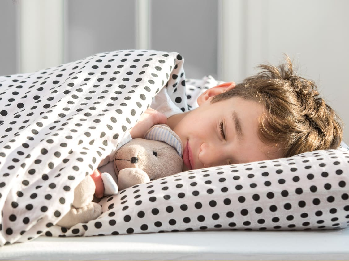 Schlafender Bub mit Hundeteddy in gepunkteter Bettwäsche