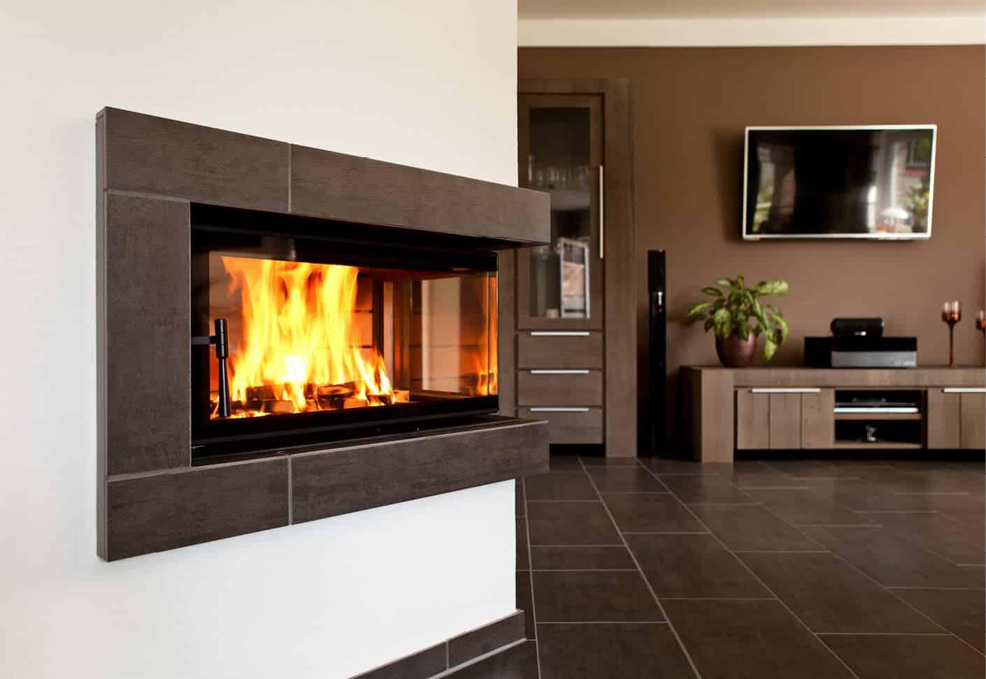 In einem Ofen brennt Feuer, dahinter ist ein Wohnzimmer
