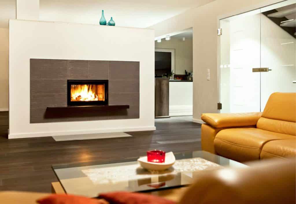 Moderner, heller Wohnraum mit Speicherofen im Zentrum