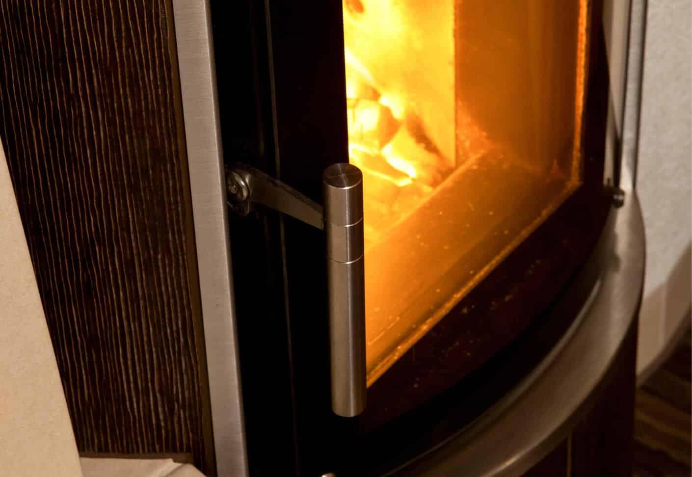 Türgriff einer Ofentüre, dahinter Feuer im Ofen