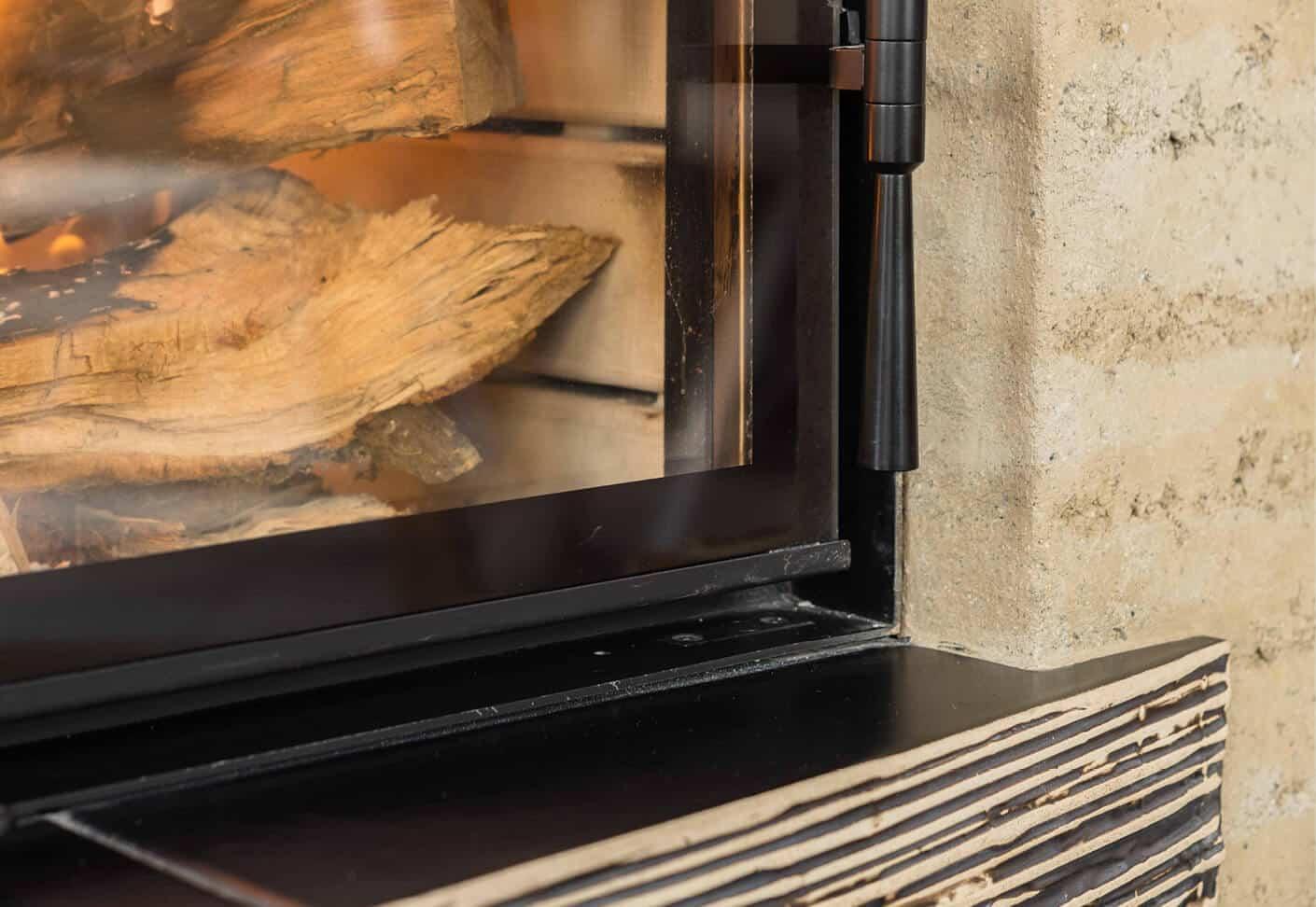 Eine Ofentüre aus Glas, im Ofen ist Holz