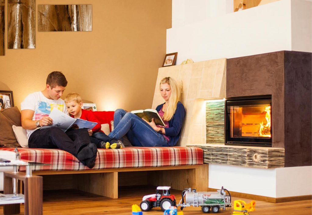 Familie sitzt bei Ofen, davor liegt Spielzeug am Boden