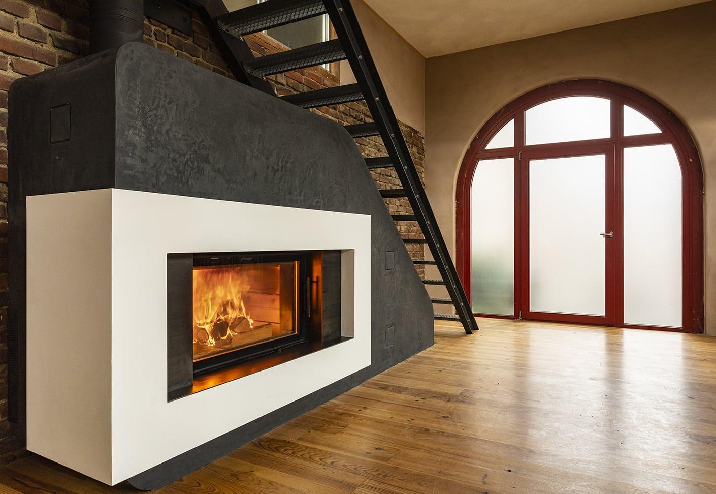 Kantiger Ofen mit großem Fenster unter einer Stiege, daneben eine Gläserne Türe.