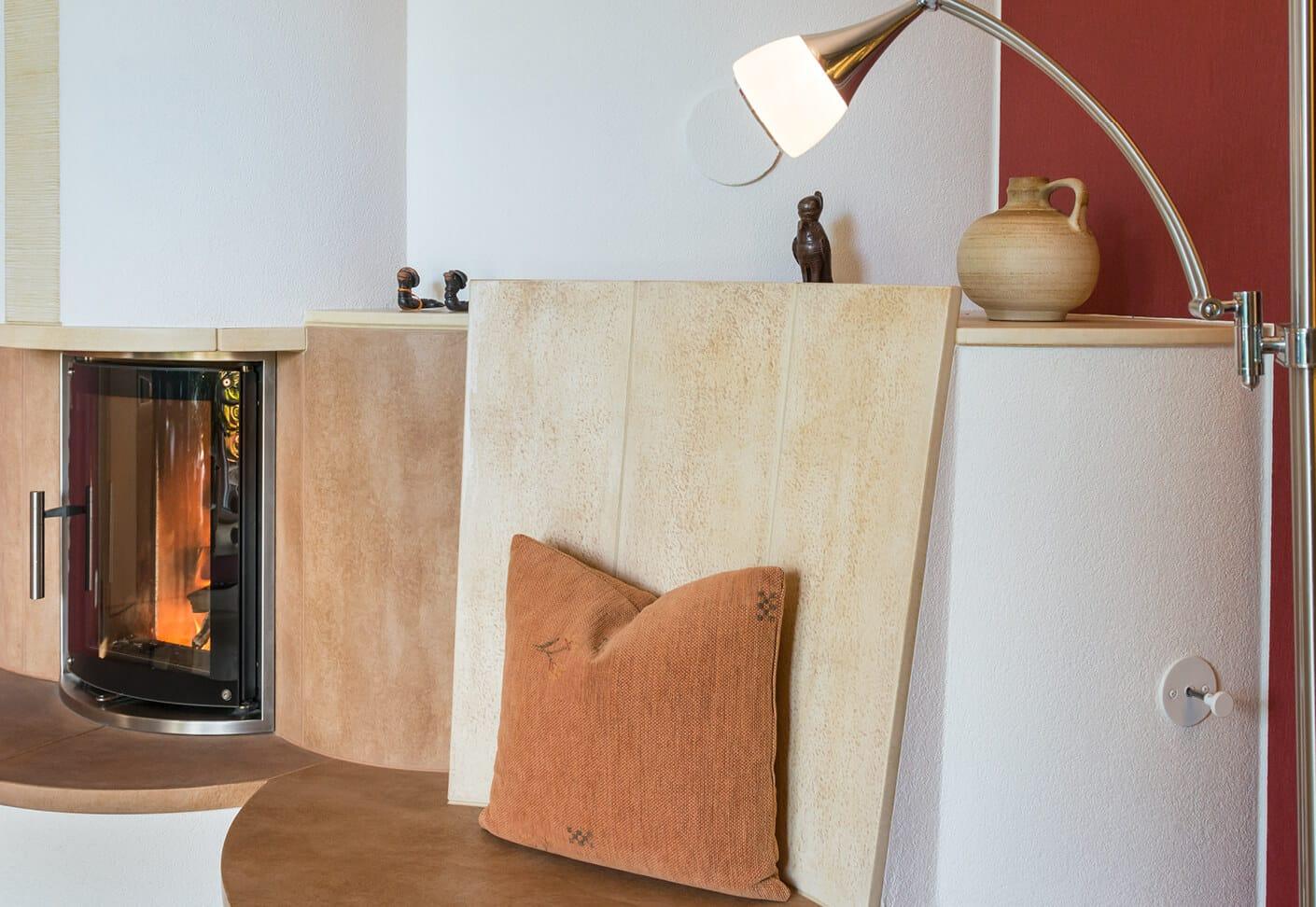 Runder Speicherofen, teilweise mit braunen Fliesen vor einer roten Wand