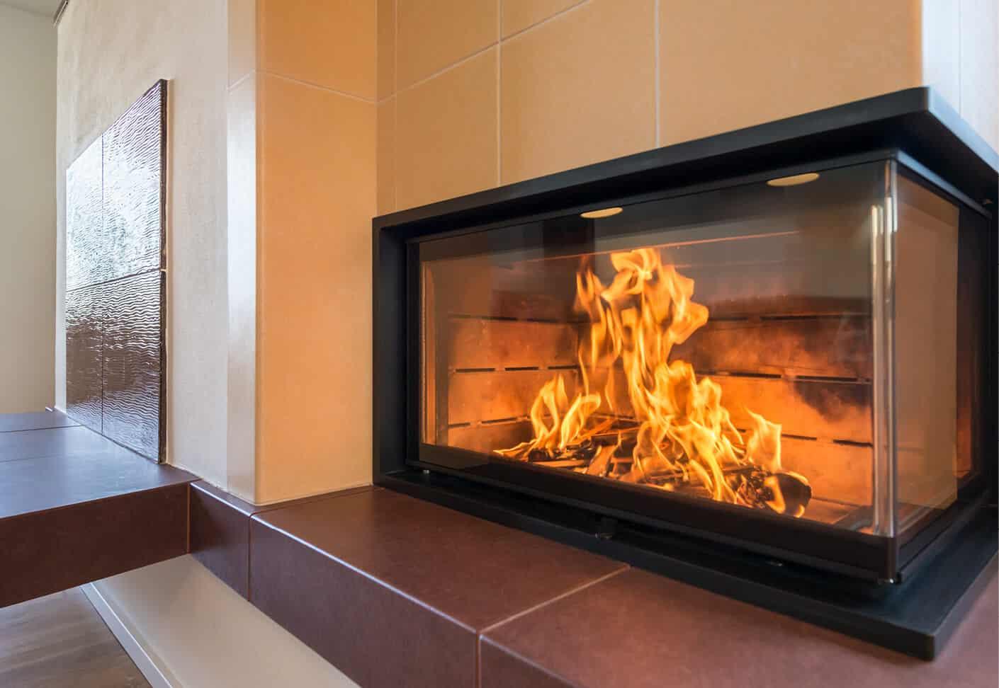 Glasfenster eines Ofen, darin brennt Feuer