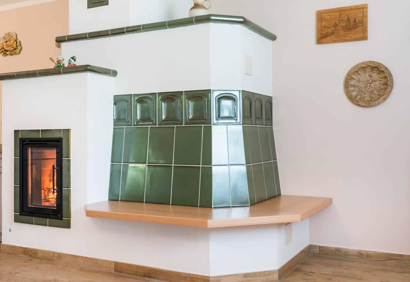 Speicherofen mit grünen Fliesen und Ofenbank