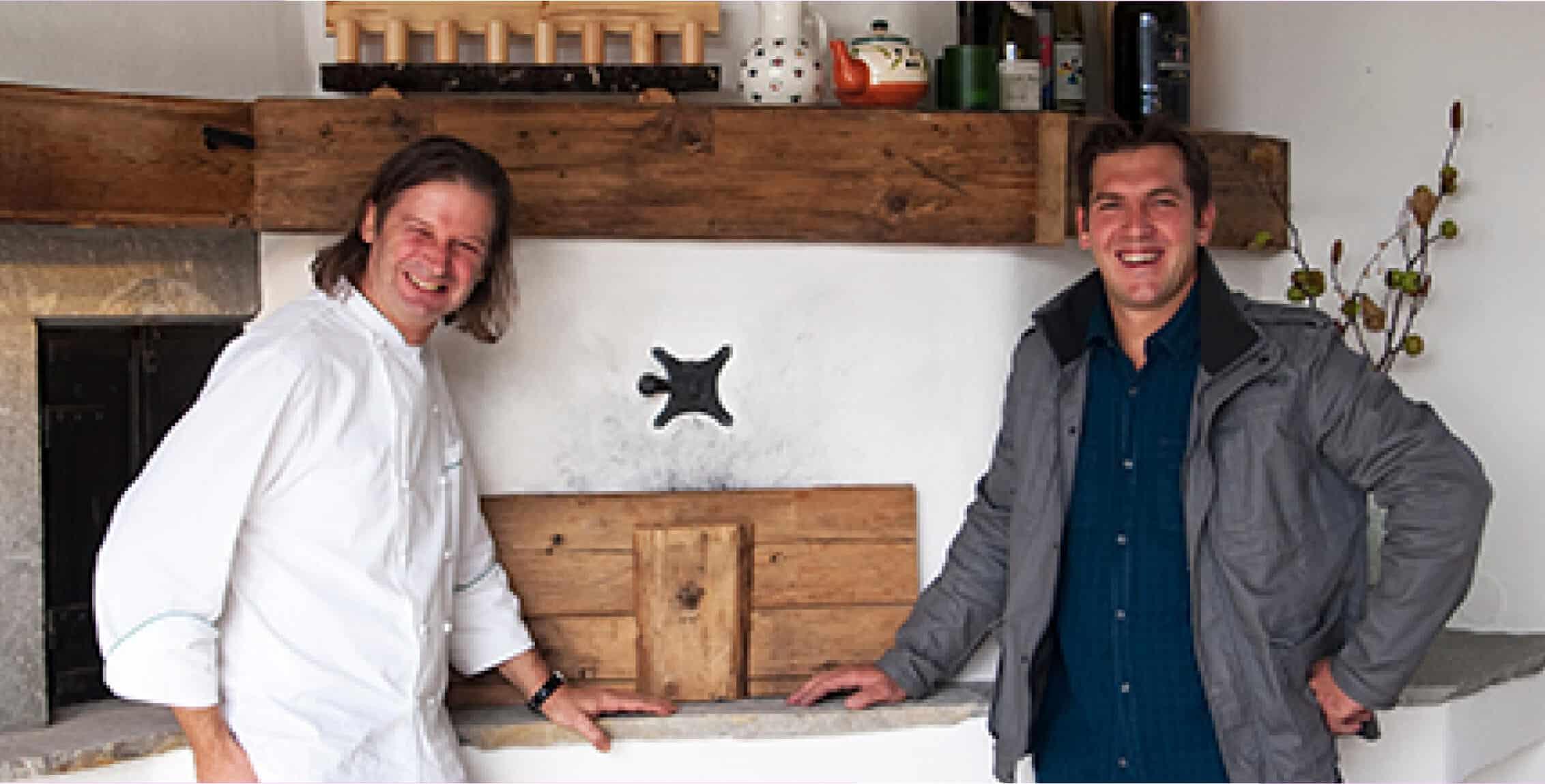 zwei Männer Stehen vor einem großen Holzbackofen
