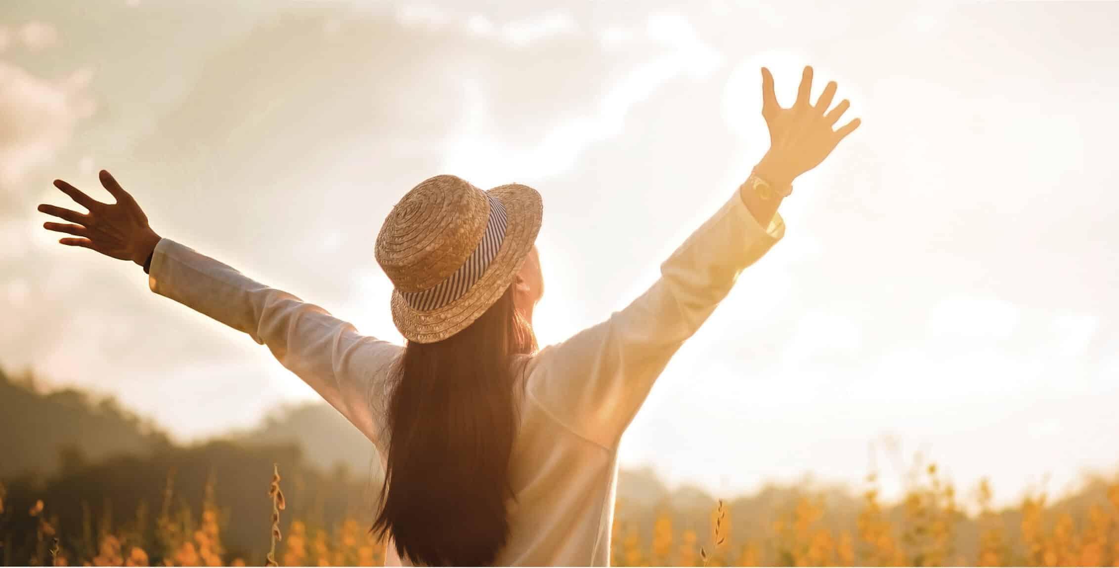 Frau in der Natur streckt ihre Arme der Sonne entgegen.