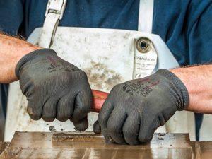 Hände eines Mannes in Arbeitshandschuhen beim Bau eines Ofens