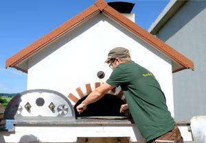 Mann reinigt Holzbackofen