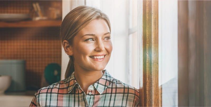 Frau lächelt aus einem Fenster hinaus