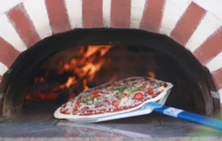 Pizza wird in eine Ofen geschoben
