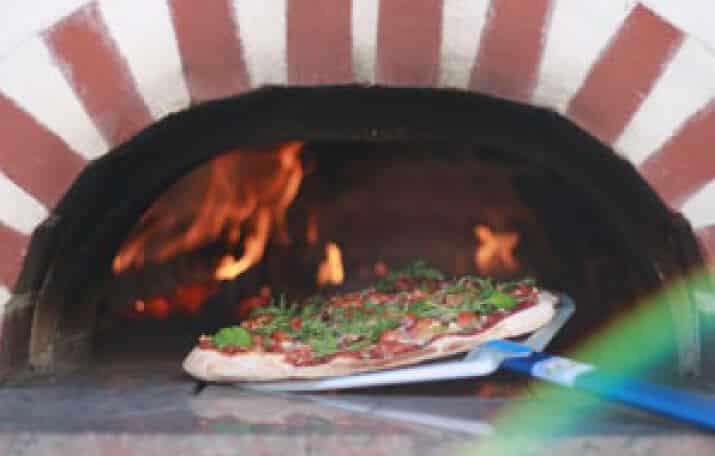 Pizza wird in einen Backofen geschoben
