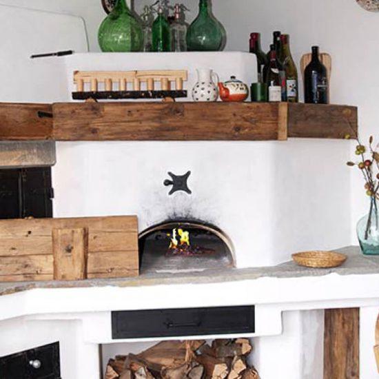 Rustikaler Holzbackofen auf dem Diverse Flaschen stehen
