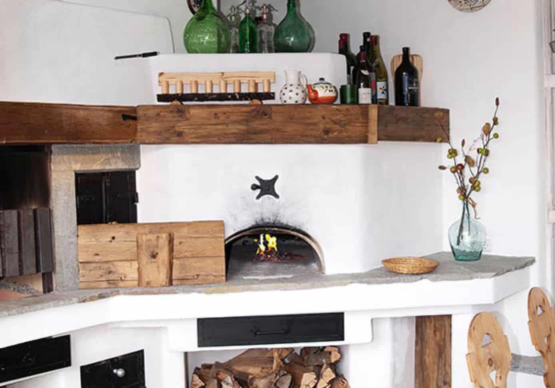 Rustikaler Holzbackofen auf dem Diverse Flaschen stehen - Holzbackofen Gestaltung