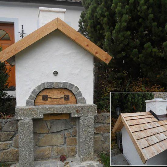 Holbackofen vor einem Haus neben einer Hecke
