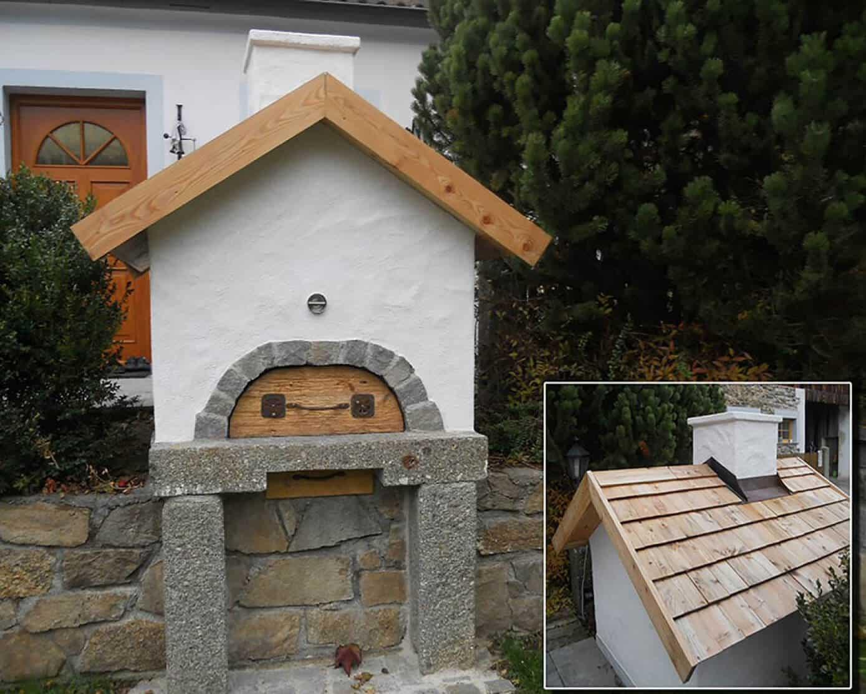 Holbackofen vor einem Haus neben einer Hecke - Holzbackofen Gestaltung