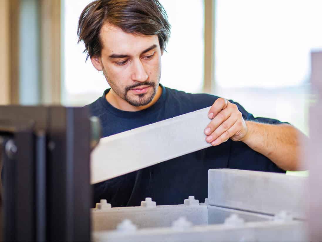 Ein junger Mann legt Steine eines Ofens übereinander