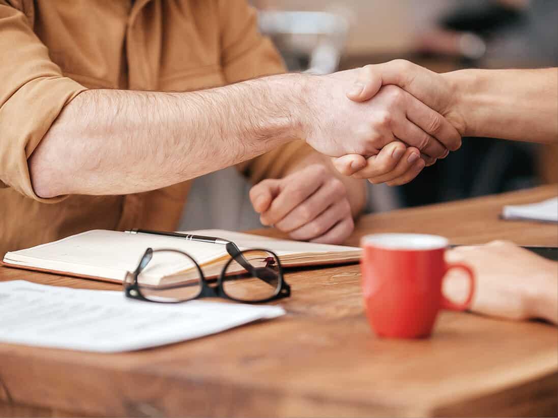 Zwei Menschen geben sich die Hand, Brille und Tasse sind am Tisch