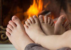 Zwei Paar Füße vor einem Ofenfeuer
