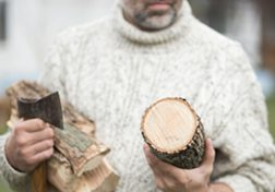 Mann hält Holz und Axt in den Händen