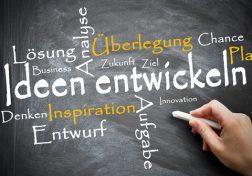 Eine Hand schreibt Wörter auf eine Tafel