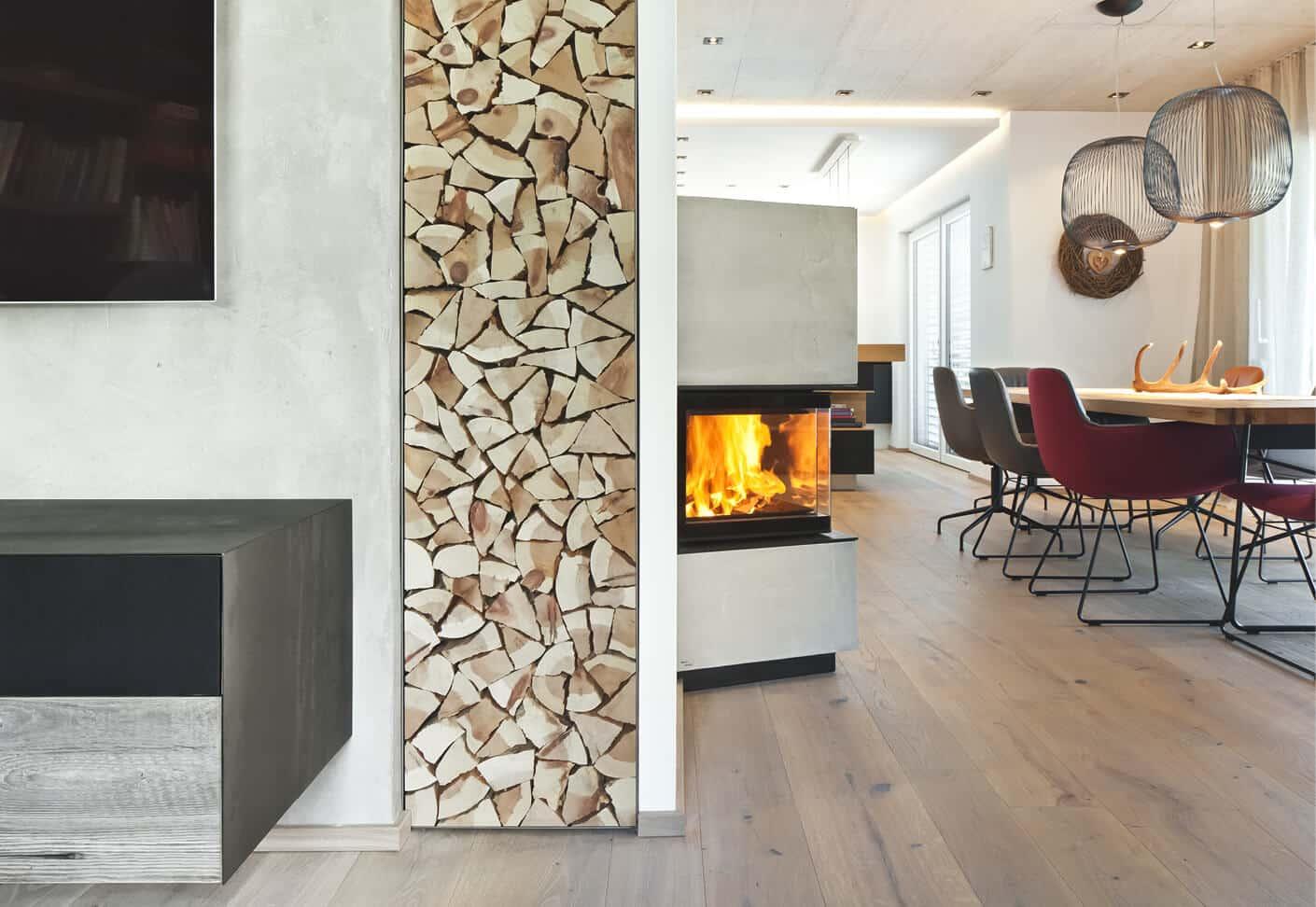Speicherofen, daneben hoher Holzstoß in einem modernem Wohnraum