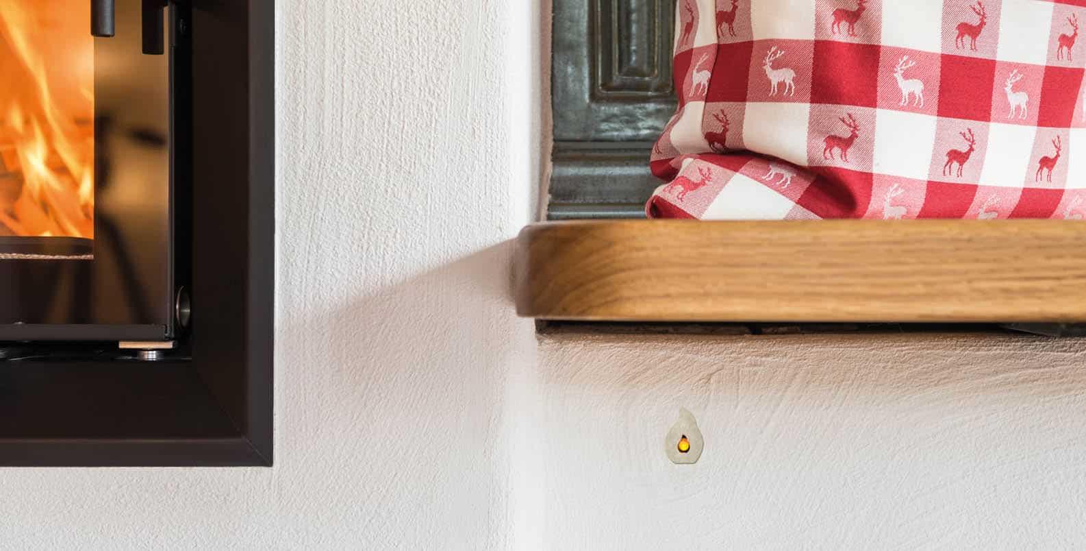 Gemütliche Ofenbank neben dem Feurraum. Neben dem Sichtfenster sieht man den LED Stecker der Abbrandsteuerung