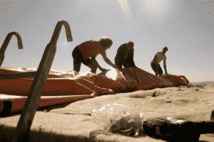 Drei Personen arbeiten auf einer Baustelle.