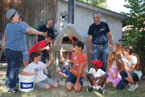 Ein Mitarbeiter der Firma ORTNER und eine Gruppe Kinder steht vor einem beheizten ORTNER Holzbackofen.