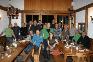 Eine größere Gruppe von Leuten sitzt in einer Gaststube.