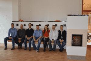 Sieben Personen sitzen auf einer langen Ofenbank.