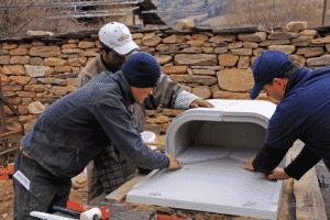 Drei Personen bauen in Bhutan einen ORTNER Holzbackofen auf.