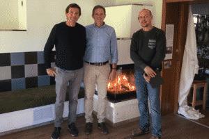 DI Manfred Huber, Geschäftsführer der ORTNER GmbH, und zwei weitere Personen stehen vor einem Speicherofen.