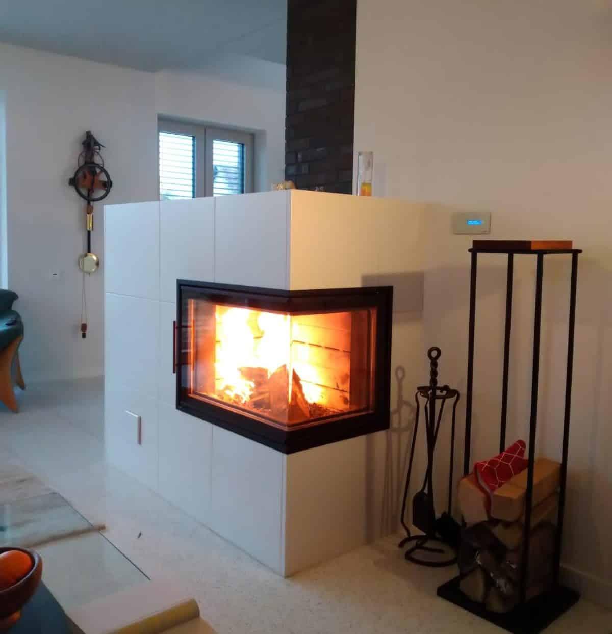 Ein Speicherofen mit weißer Keramik und in dem ein Feuer brennt. Ein Feuerbesteck steht davor.